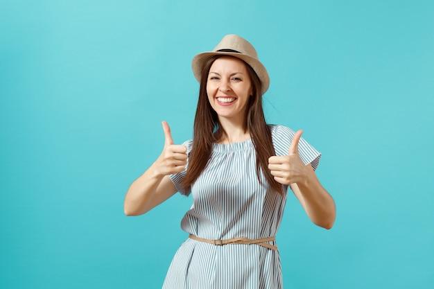 Портрет счастливой улыбающейся женщины нося платье, соломенная летняя шляпа показывает большие пальцы руки вверх, большие пальцы руки сигнализируют о копировании пространства, изолированном на синем фоне. люди искренние эмоции, концепция образа жизни. рекламная площадка.