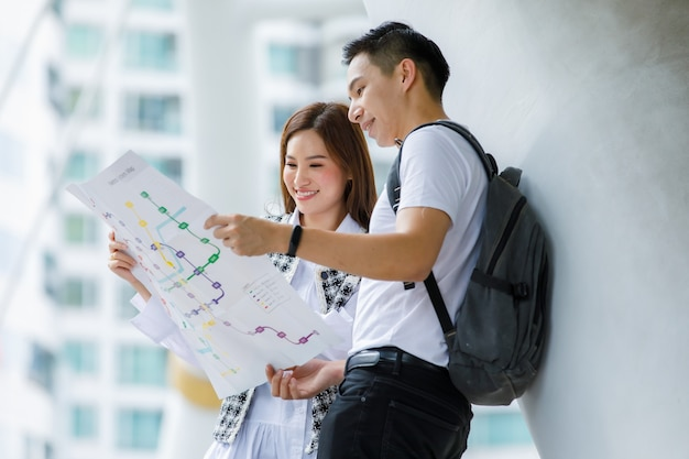 행복한 미소를 짓고 있는 아시아 젊은 성인 커플 관광객의 초상화는 서서 종이 지도를 함께 보고 높은 건물 배경으로 휴가에 관광 명소의 목적지에 대한 가이드를 찾습니다
