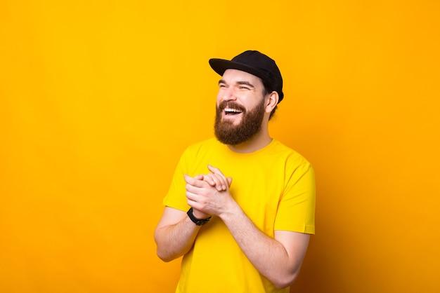 Портрет счастливого улыбающегося молодого бородатого хипстера на желтом фоне
