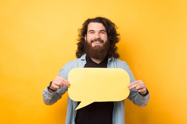 Портрет счастливого улыбающегося молодого бородатого мужчины с длинными волосами, держащего пустой желтый речевой пузырь
