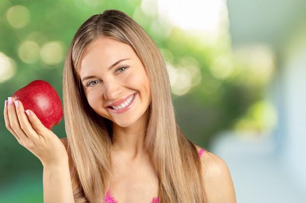 Портрет счастливой улыбкой молодая красивая женщина ест красное яблоко