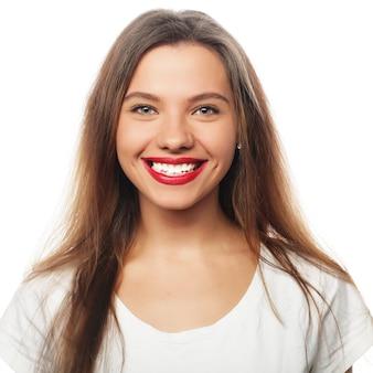 ホワイトスペースで分離された幸せな笑顔若い美しい女性の肖像画
