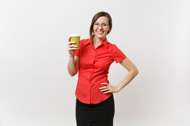 白い背景で隔離の手でコーヒーやお茶のカップを保持している赤いシャツのメガネで幸せな笑顔の若いビジネス教師の女性の肖像画。高校の大学の概念における教育または教育。