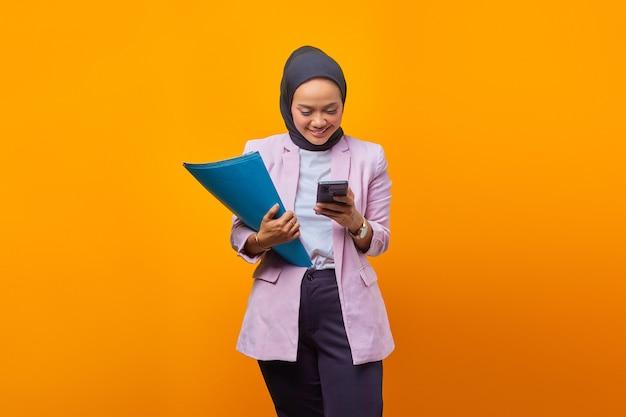 폴더를 들고 노란색 배경 위에 스마트폰을 사용하는 행복한 미소 짓는 젊은 비즈니스 여성의 초상화