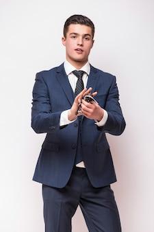 白い壁に分離された青いスーツの幸せな笑顔の若いビジネスマンの肖像画