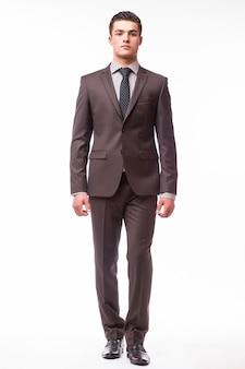白い壁に分離された茶色のスーツの幸せな笑顔の若いビジネスマンの肖像画