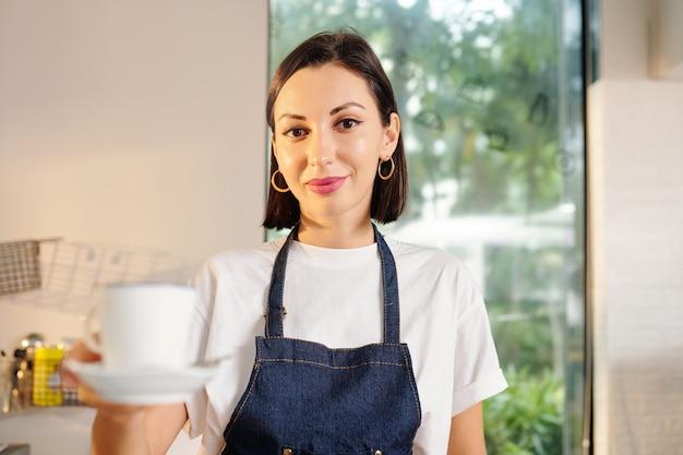 Портрет счастливой улыбающейся молодой официантки кафе, предлагающей чашку свежего кофе