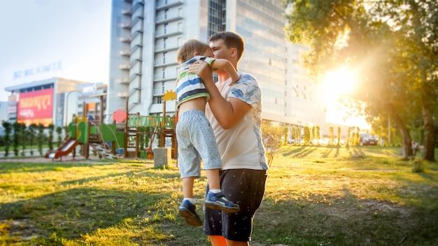 Портрет счастливого улыбающегося молодого отца, держащего и рвущего своего смеющегося трехлетнего маленького сына в парке на суснете