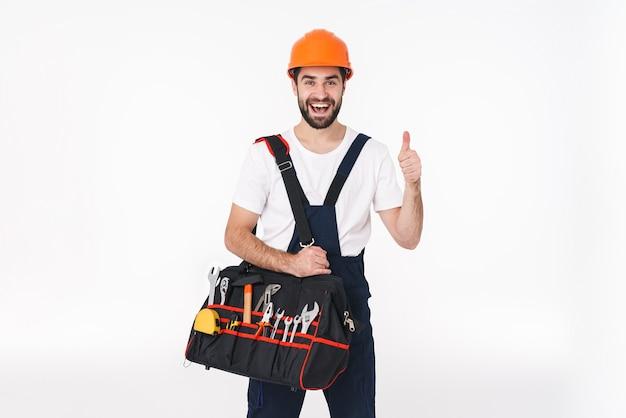 親指を上に表示している機器の楽器とバッグを保持している白い壁の上に分離されたヘルメットの幸せな笑顔の若い男のビルダーの肖像画。