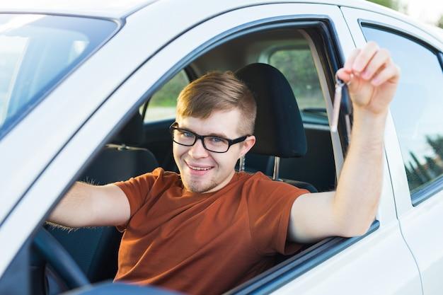 웃는 젊은 남자의 초상화, 새 차에 앉아 딜러 사무실 밖에 열쇠를 보여주는 구매자. 개인 운송, 자동 구매 개념.