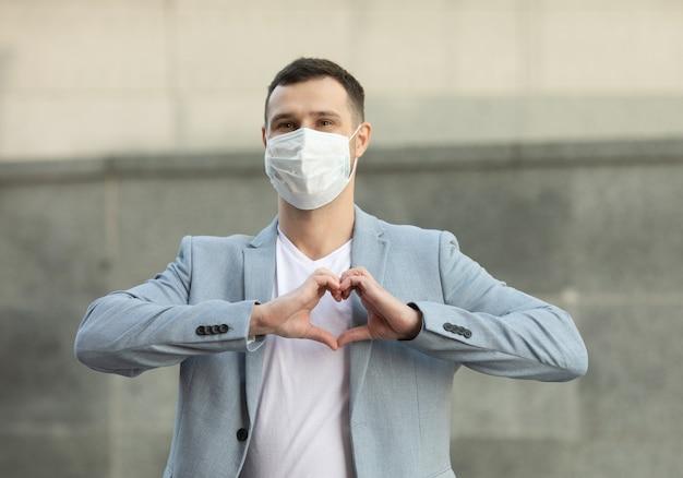 愛のジェスチャーで立っている外科医療マスクを持つ幸せな笑顔の若い男の肖像画