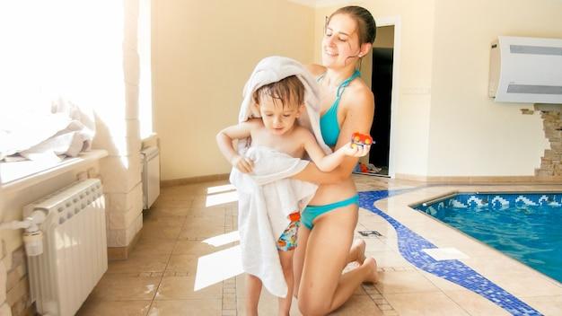수영장에서 수영한 후 큰 흰색 수건으로 어린 아들을 닦고 워밍업하는 행복한 미소 짓는 젊은 어머니의 초상화