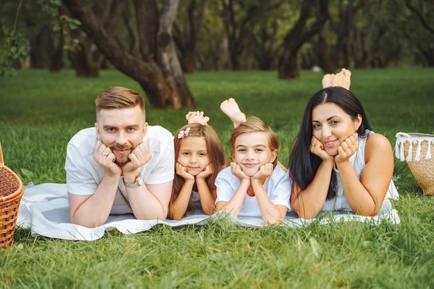 晴れた日にピクニック毛布の上に一緒に横たわっている幸せな笑顔の若い親と2人の子供の肖像画。愛、家族、幸せな子供時代のライフスタイルの概念