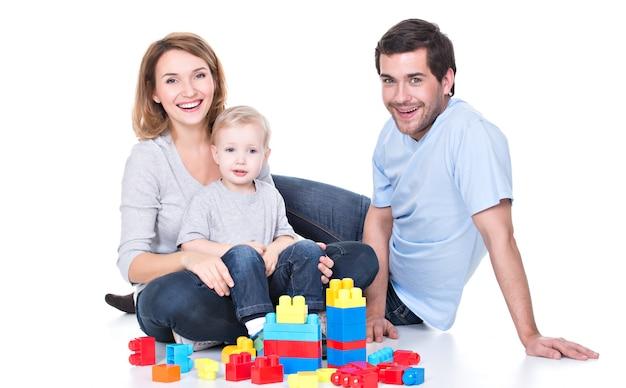 赤ちゃんと遊ぶ幸せな笑顔の若い親の肖像画-白で隔離