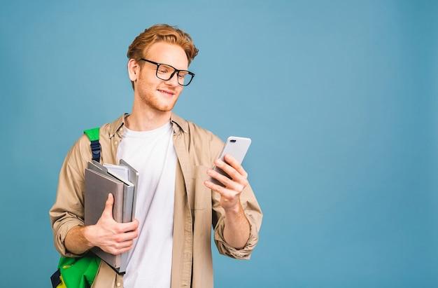 Портрет счастливого улыбающегося молодого студента, стоящего с рюкзаком и папками. с помощью мобильного телефона.