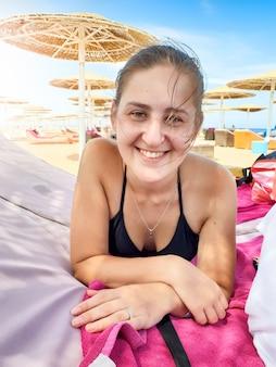 Портрет счастливой улыбающейся молодой женщины с длинными волосами, лежащей на шезлонге под зонтиком на берегу океана и смотрящей в камеру