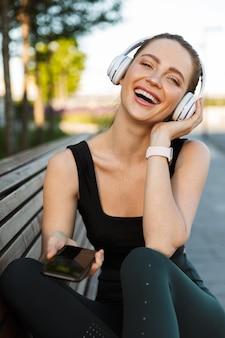 Портрет счастливой спортсменки в спортивном костюме, держащей смартфон и слушающей музыку в наушниках, сидя на скамейке в городском парке