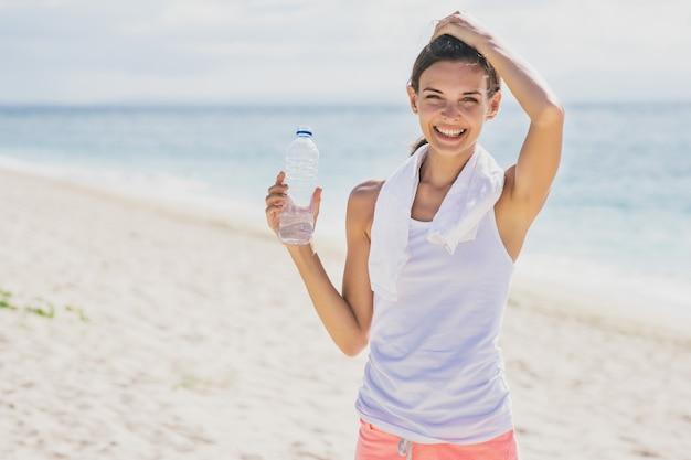 해변에서 다과를 위해 미네랄 워터 한 병을 들고 행복 스포티 한 여자의 초상화