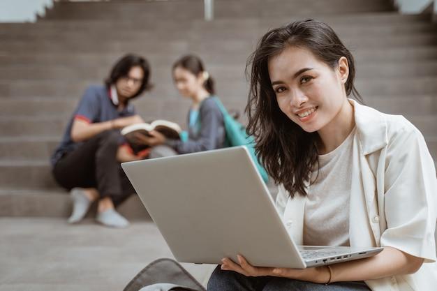 Портрет счастливых студентов, держащих ноутбуки с друзьями на заднем плане