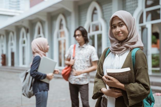 Портрет счастливых студентов, смотрящих на фронт во дворе кампуса