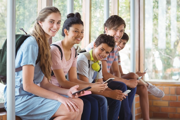 窓枠に座っていると廊下で携帯電話を使用して幸せな学生の肖像画