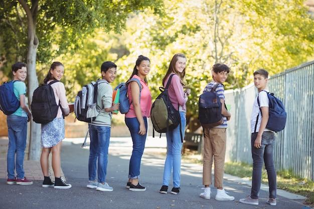道路上のバックパックで立っている幸せな学生の肖像画