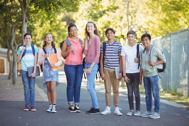 道路上の本で立っている幸せな学生の肖像画