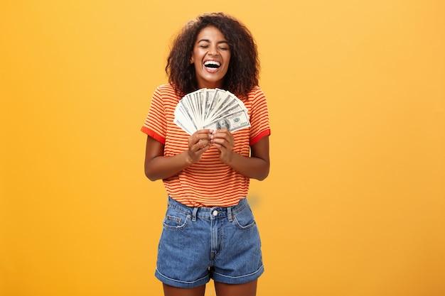 たくさんのお金を保持している最初の支払いを受け取る幸せなスタイリッシュな若い女性の肖像画。