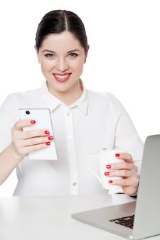 座って、飲み物、スマートフォンを保持し、歯を見せる笑顔で見ている白いシャツで幸せな成功した魅力的なブルネットの実業家の肖像画。白い背景で隔離の屋内スタジオショット。