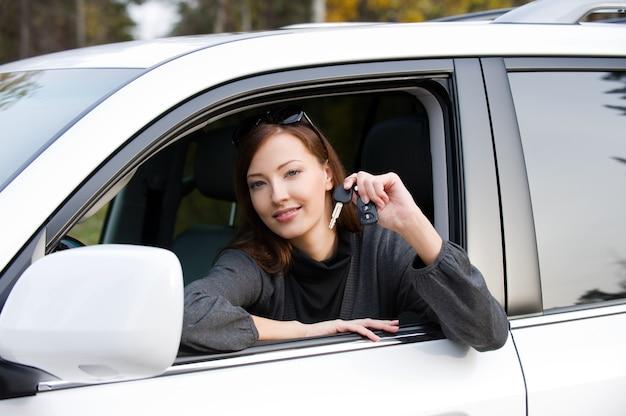 新しい車からのキーを持つ幸せな成功した女性の肖像画-屋外