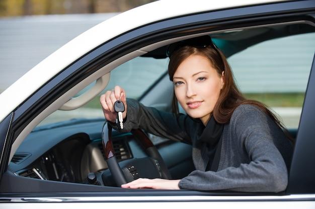 새 차에서 키와 함께 행복 한 성공적인 여자의 초상화-야외