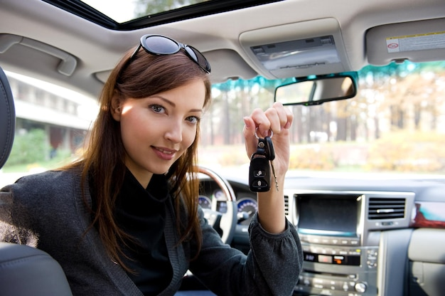 새 차에서 키와 함께 행복 한 성공적인 여자의 초상화