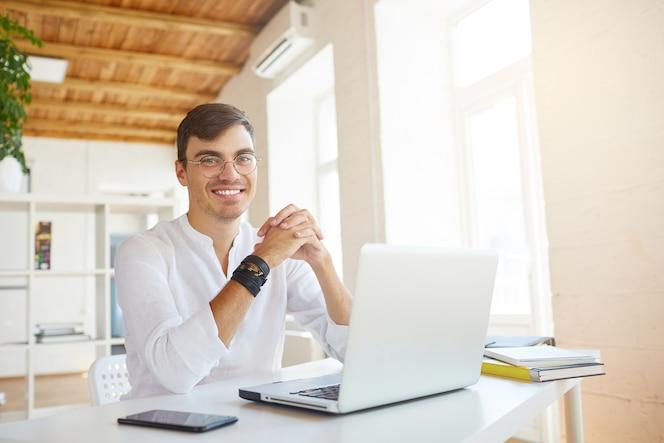 幸せな成功した青年実業家の肖像画は、オフィスで白いシャツを着ています