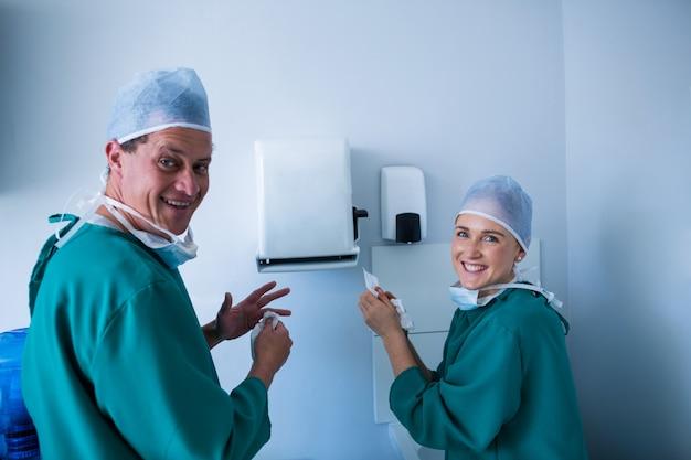 手術後の手をきれいにする幸せな外科医の肖像画
