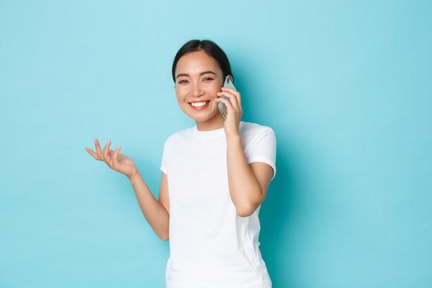 Портрет счастливой удивленной азиатской девушки, улыбающейся и поднимающей руку во время телефонного разговора, разговаривающей с кем-то, выглядящей довольной хорошими новостями, стоящей в повседневной футболке над голубой стеной