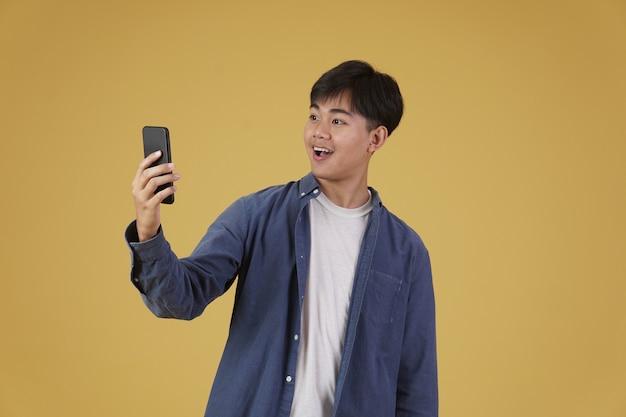 행복 놀란 흥분된 젊은 아시아 남자의 초상화는 부담없이 고립 된 스마트 폰보고 옷을 입고