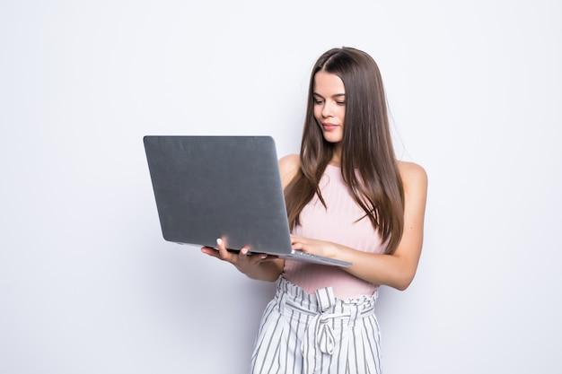 회색 벽에 고립 된 노트북으로 서 행복 놀된 여자의 초상화.