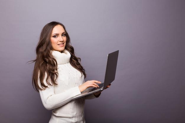 회색 벽에 고립 된 노트북으로 서 행복 놀란 여자의 초상화