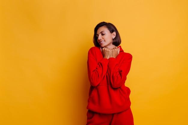 トレンディな暖かい赤いフリースのパーカーとパンツを着て、寒い冬の準備をしている幸せな日焼けフィットの女性の肖像画