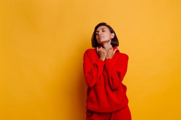 Портрет счастливой загорелой женщины в модной теплой красной флисовой толстовке и брюках
