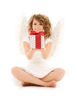 Портрет счастливой девочки-ангела с подарком над белой стеной
