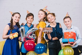 Portrait of happy teenage friends enjoying the birthday by holding birthday cake; gifts and number 14 foil balloon