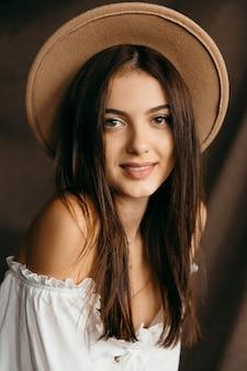 Портрет счастливой девочки-подростка на изолированной коричневой предпосылке. фото высокого качества