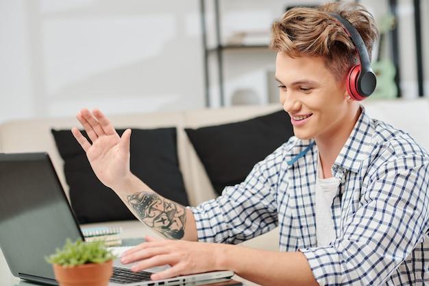Портрет счастливого подростка в наушниках, видео звонящего своим друзьям, оставаясь дома