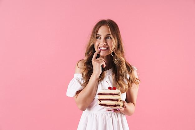 彼女の指で彼女の歯を上向きに見ている白いドレスを着て、ピンクの壁に隔離されたケーキを保持している幸せな思考の女性の肖像画
