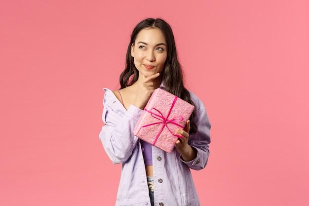 Портрет счастливой задумчивой молодой азиатской девушки получает завернутую коробку с подарком, удивляется, что спрятано внутри, пытается угадать, улыбается и смотрит, думая заинтригованно