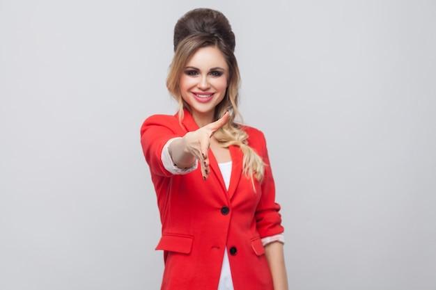 Портрет счастливой зубастой улыбающейся красивой бизнес-леди с прической и макияжем в красном модном пиджаке, стоящей, смотрящей на камею и протягивающей руку приветствию. студия выстрел, изолированные на сером фоне.