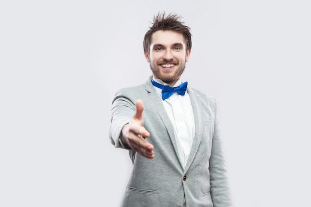 Портрет счастливого зубастого смайлика красивого бородатого мужчины в повседневном сером костюме, синем галстуке-бабочке, стоящем, смотрящем и протягивающем руку для приветствия или рукопожатия. закрытый студийный снимок, изолированные на светло-сером фоне