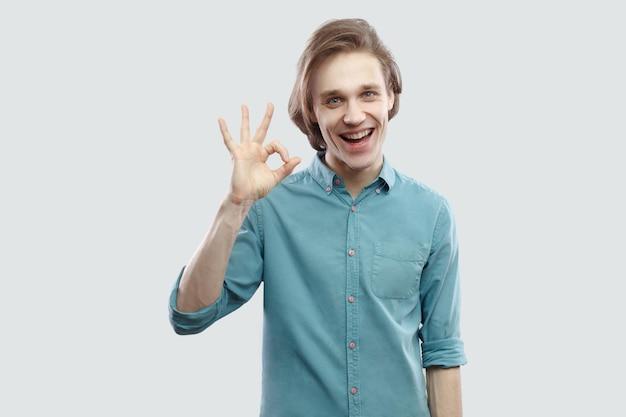 파란 캐주얼 셔츠를 입고 서서 확인 제스처로 카메라를 바라보는 행복한 이빨 웃는 잘생긴 장발 금발 청년의 초상화. 밝은 회색 배경에 격리된 실내 스튜디오 촬영.