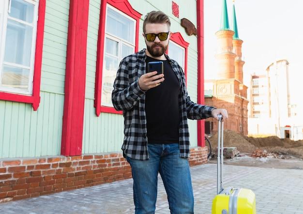 도시의 건물 근처에 가방을 들고 서 있는 행복한 여행 남자의 초상화